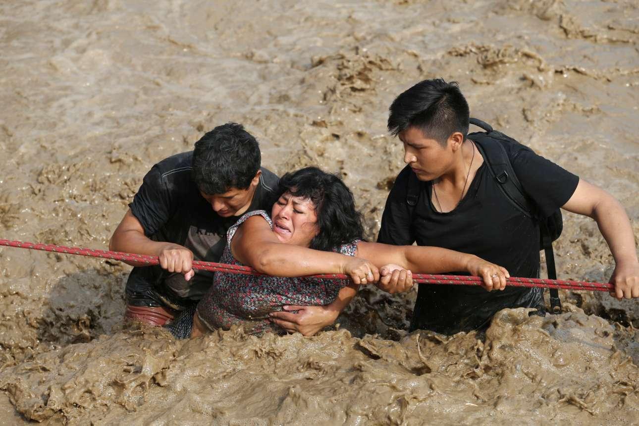 17 Μαρ. Μία γυναίκα προσπαθεί με τη βοήθεια ενός σκοινιού και δύο νεότερων ανδρών να διασχίσει έναν δρόμο που πλημμύρισε όταν υπερχείλισε ο ποταμός Χουάικο, στέλνοντας τόνους νερού και χώματος στην πόλη Χουατσίπα, στο Περού