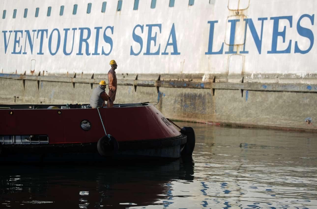 Οι εργάτες κοιτούν για τελευταία φορά το πλοίο που εδώ και καιρό παρέμεινε μισοβυθισμένο