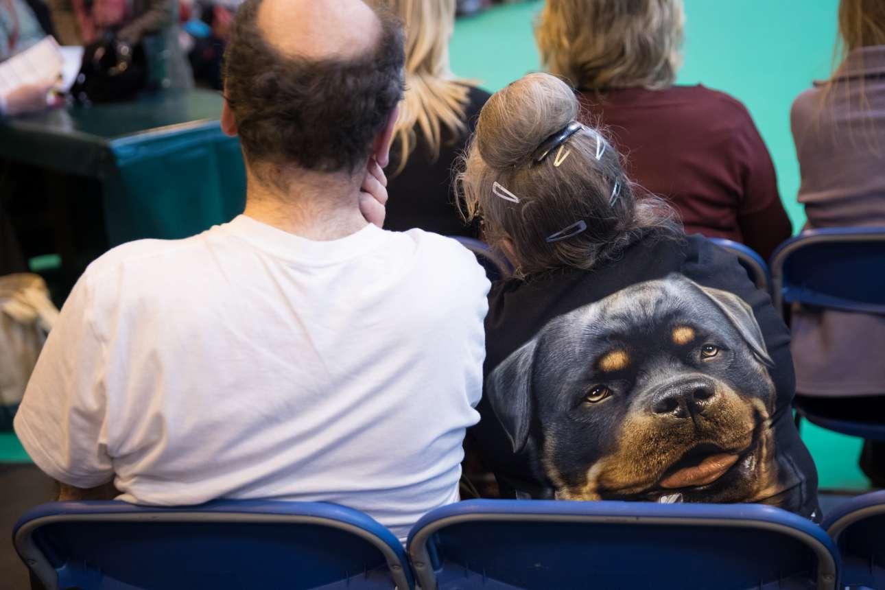 Φορώντας μια μπλούζα με τεράστια στάμπα σκύλου πάνω, μια γυναίκα παρακολουθεί τα αγωνίσματα