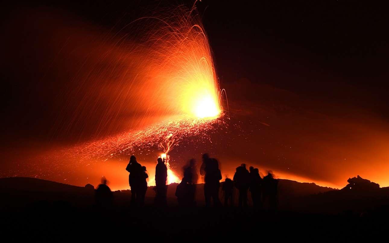 Τουρίστες παρακολουθούν το ηφαίστειο Αίτνα να εκτοξεύει λάβα αργά το βράδυ της 21ης Ιουλίου του 2006