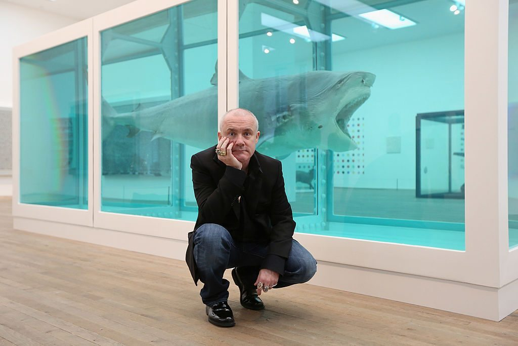 LONDON, ENGLAND - APRIL 02: Artist Damien Hirst poses in front of his artwork entitled 'The Physical Impossibility of Death in the Mind of Someone Living' in the Tate Modern art gallery on April 2, 2012 in London, England. The Tate Modern is displaying the first major exhibition of Damien Hirst's artworks in the UK, bringing together the collection over 70 of Hirst's works spanning three decades. The exhibition opens to the general public on April 4, 2012 and runs until September 9, 2012. (Photo by Oli Scarff/Getty Images)
