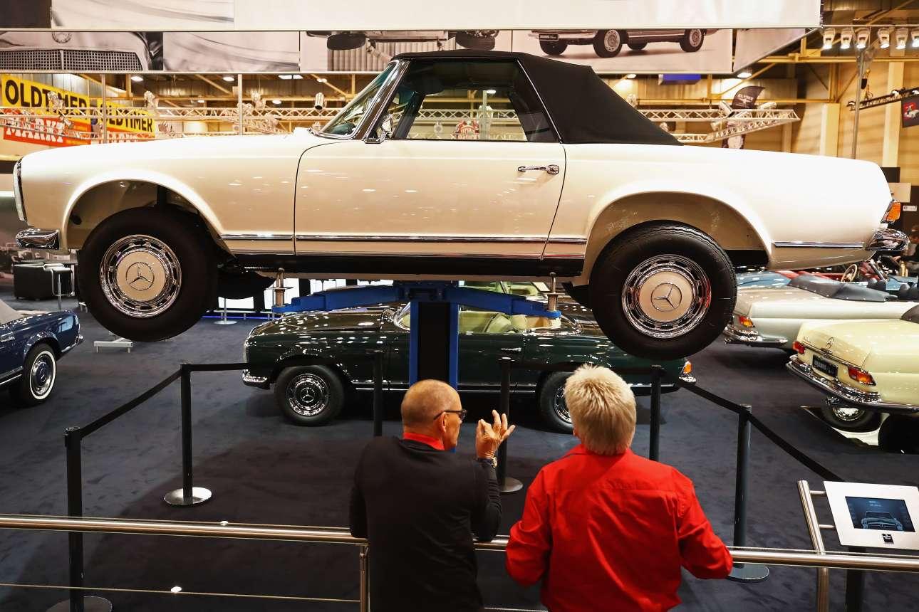 Επισκέπτες θαυμάζουν μία Mercedes-Benz 280 SL