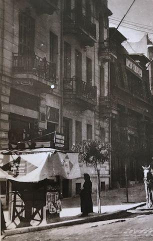 Φωτογραφία τραβηγμένη από τη γωνία Τσιμισκή και Αγίας Σοφίας. Το δεύτερο κτίριο φιλοξενούσε την Ένωση Συντακτών στον πρώτο όροφο, και στο ισόγειο , με την ιδιότυπη αρχιτεκτονική του, τον κινηματογράφο «Διονύσια», όπου το 1938 ο μικρός μαθητής Μανόλης Αναγνωστάκης με την παρέα του έβλεπε ταινία, δίπλα στους προπολεμικούς άσους της ΑΕΚ και του ΠΑΟΚ.