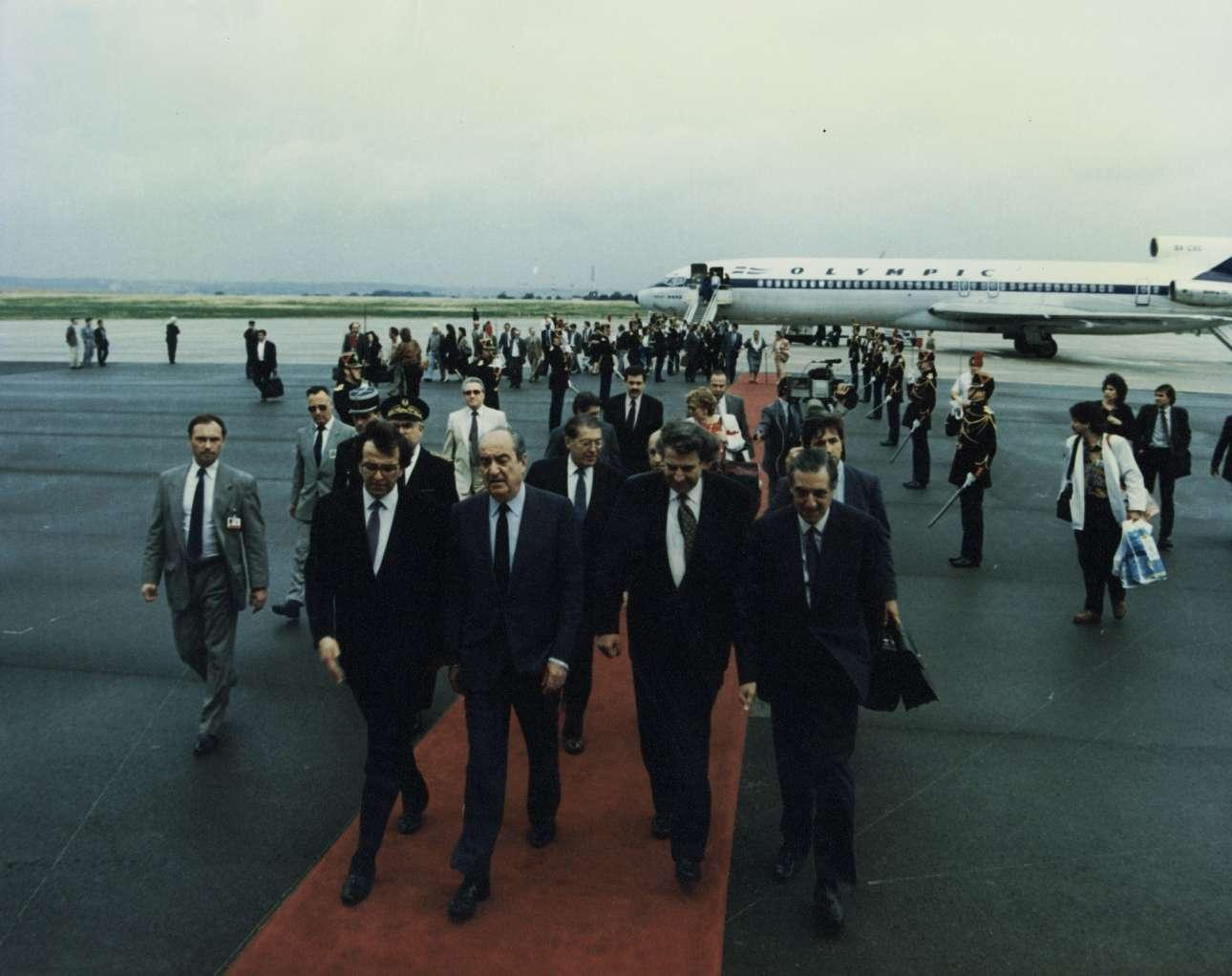 Αφιξη του Κωνσταντίνου Μητσοτάκη στο Παρίσι για επίσημη επίσκεψη, Ιούνιος του 1990. Αριστερά του ο τότε υπ. Εξωτερικών Αντώνης Σαμαράς. Δεξιά του Μίκης Θεοδωράκης, τότε υπουργός Ανευ Χαρτοφυλακίου