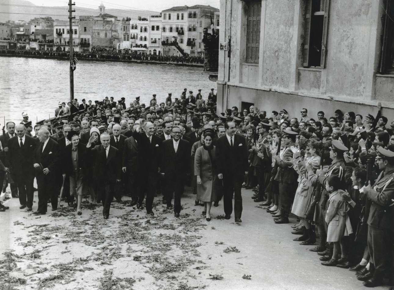 1η Δεκεμβρίου 1963 ο Μητσοτάκης στα Χανιά, στους εροτασμούς για τα 50 χρόνια από την ένωση της Κρήτης με την Ελλάδα. Ο τότε πρωθυπουργός Γεώργιος Παπανδρέου, περιστοιχισμένος από τον αντιπρόεδρο της Κυβέρνησης, Σοφοκλή Βενιζέλο και τους υπουργούς του οδεύει προς το φρούριο Φιρκά, όπου έγινε έπαρση σημαίας. Διακρίνονται επίσης η Μαρίκα Μητσοτάκη και η Δέσποινα Βενιζέλου.