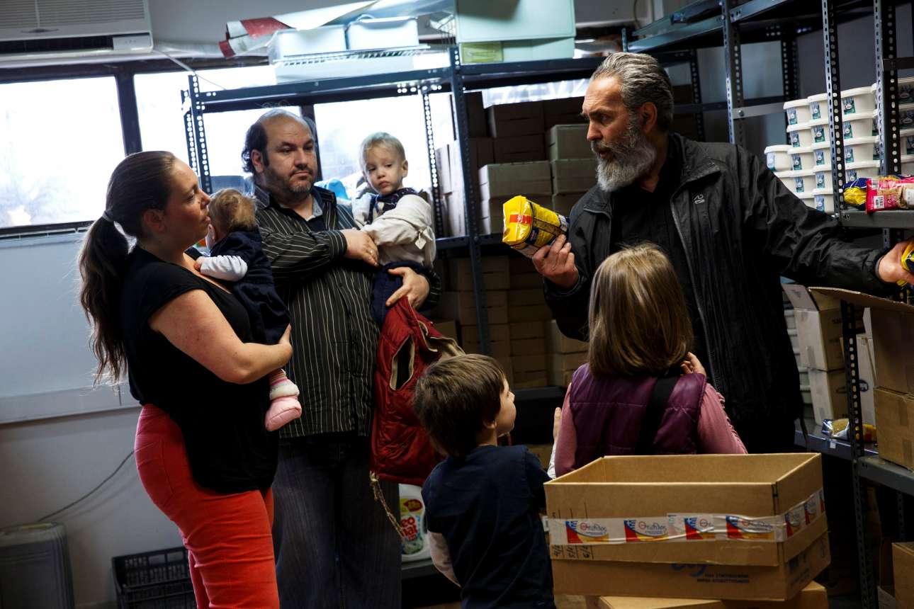 H οικογένεια λαμβάνει τρόφιμα από τον φιλανθρωπικό οργανισμό «Θεόφιλος» που στηρίζει πολύτεκνες οικογένειες στην χώρα μας