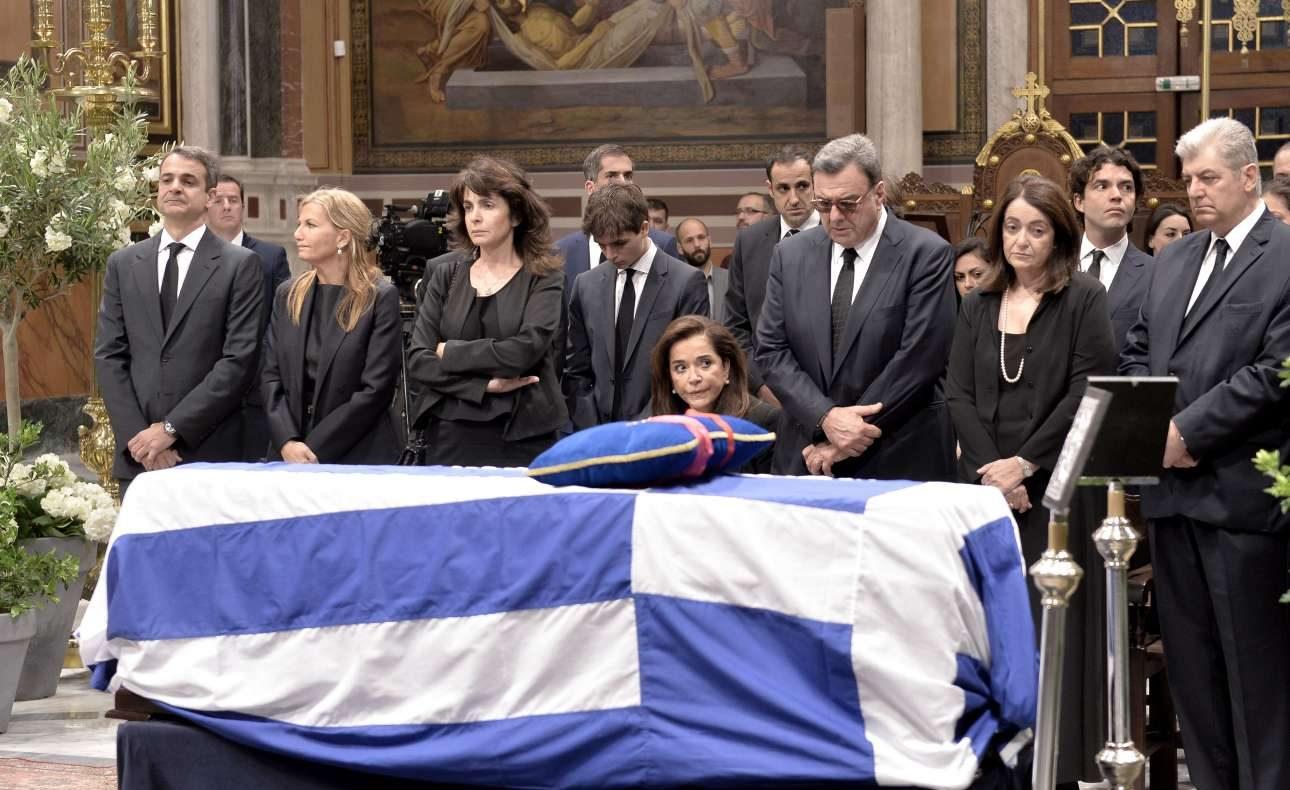 Η οικογένεια μπροστά από το φέρετρο. Η Ντόρα Μπακογιάννη κάθεται καθώς πρόσφατα υποβλήθηκε σε χειρουργική επέμβαση στο πόδι
