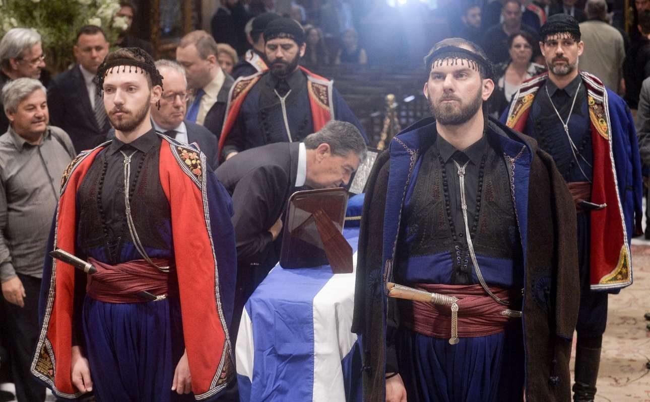 Τέσσερις άνδρες με παραδοσιακές κρητικές φορεσιές συνοδεύουν το φέρετρο. Πλήθος κόσμου από νωρίς στη Μητρόπολη
