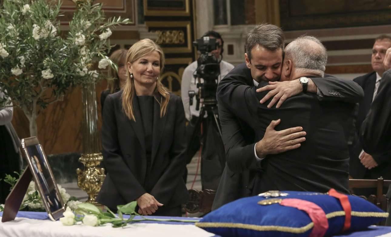 Μεσημέρι. Ο Κυριάκος Μητσοτάκης συνεχίζει να δέχεται τα συλλυπητήρια των απλών πολιτών που σπεύδουν να αποχαιρετήσουν τον πατέρα του. Δίπλα του η Μαρέβα