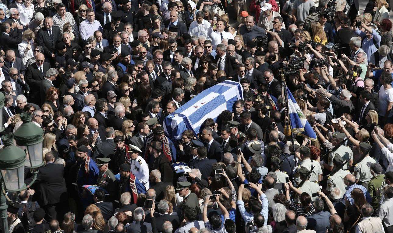 Σκεπασμένο με την ελληνική σημαία, το φέρετρο του Κωνσταντίνου Μητσοτάκη μεταφέρεται έξω από τον ναό. Αμέτρητα κινητά τηλέφωνα απαθανατίζουν τις στιγμές