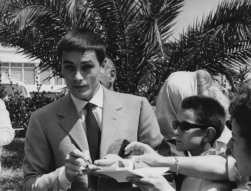 French actor Alain Delon signs autographs for young fans in Cannes during the film festival, 11th May 1961. (Photo by Keystone/Hulton Archive/Getty Images)