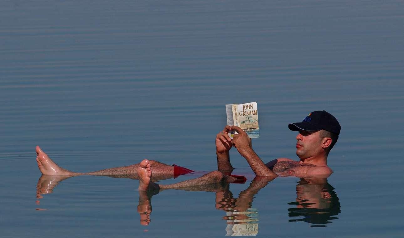 Λόγω της υψηλής συγκέντρωσης αλάτων, η εμπειρία της κολύμβησης εκεί είναι μοναδική, καθώς απλώς επιπλέεις. Στην φωτογραφία, ένας τουρίστας απολαμβάνει το βιβλίο του χωρίς κάποιο στρώμα, μόνο με την άνωση...