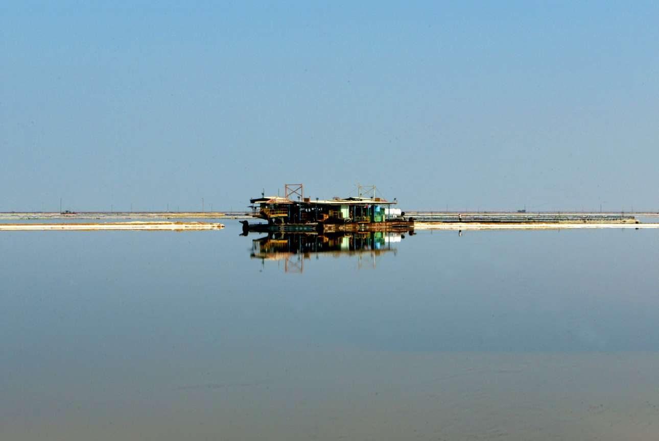 Μία βυθοκόρος καθρεφτίζεται στην ήρεμη επιφάνεια του νερού στις νότιες ακτές της Νεκράς Θάλασσας, κοντά στην πόλη Σόδομα. Σε εκείνη την περιοχή βρίσκεται το «Dead Sea Works», ο έβδομος μεγαλύτερος παραγωγός και προμηθευτής προϊόντων χλωριούχου καλίου, όπου εργάζονται περισσότερο από 10.000 ισραηλινοί