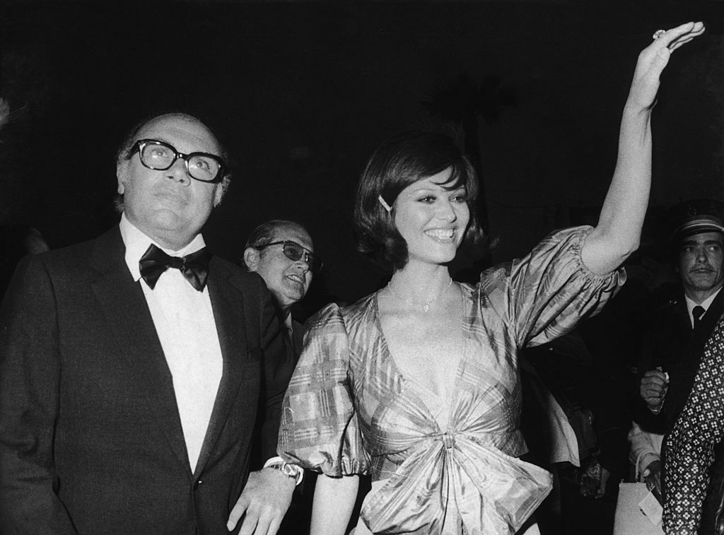 Italian director Francesco Rosi presents his film 'Il Caso Mattei' at the Cannes Film Festival, with the assistance of Italian actress Claudia Cardinale, 13th May 1972. (Photo by Keystone/Hulton Archive/Getty Images)