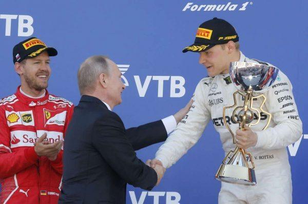 30 Απριλίου, ο Βλαντίμιρ Πούτιν βραβεύει τον Βαλτέρι Μπότας, θριαμβευτή οδηγό της Mercedes στο γκραν πρι του Σόσι. Αριστερά ο Σεμπάστιαν Φέτελ, οδηγός της Ferrari που τερμάτισε δεύτερος... (REUTERS/ Sergei Karpukhin)