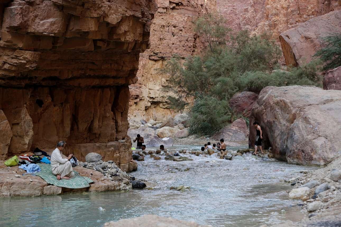Αντρες κολυμπούν σε ένα ποτάμι στην κοιλάδα του Αλ Ζάρα στην Ιορδανία, το οποίο καταλήγει στη Νεκρά Θάλασσα