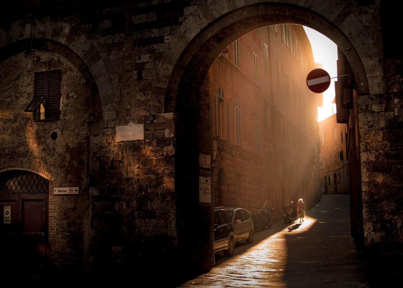 «Μεγαλειώδης σιωπή στην Σιένα». Μία πολύ ατμοσφαιρική φωτογραφία. Μία ηλικιωμένη κυρία κάνει βόλτα το ξημέρωμα στα γραφικά στενά και κάτω από τις αψίδες της πανέμορφης ιταλικής πόλης