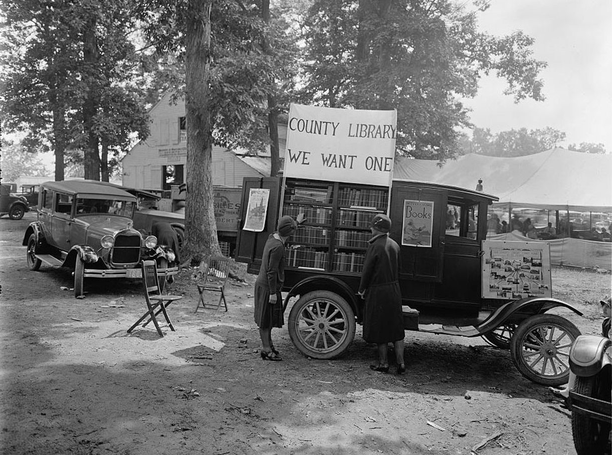 «Θέλουμε μία δημοτική βιβλιοθήκη» γράφει το πανό που έχει αναρτηθεί πάνω στο όχημα της κινητής βιβλιοθήκης, με την οποία εξυπηρετούνταν το 1928 οι κάτοικοι του Μέριλαντ των ΗΠΑ