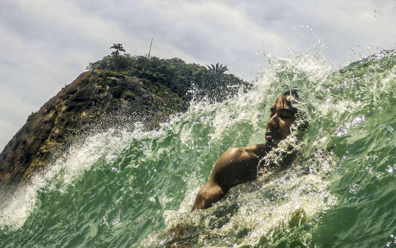 «Βραζιλιάνος σέρφερ αφήνει ένα κύμα να περάσει». Μια ιδανική μέρα για σερφ στη διάσημη παραλία Κοπακαμπάνα του Ρίο ντε Τζανέιρο, ο άνδρας της φωτογραφίας αποφασίζει να αφήσει ένα κύμα να περάσει, κάνοντας διάλειμμα από το σερφ. Ο φωτογράφος που παρακολουθούσε τον έμπειρο σέρφερ για ώρα, απαθανατίζει ένα στιγμιότυπο καθαρής απόλαυσης