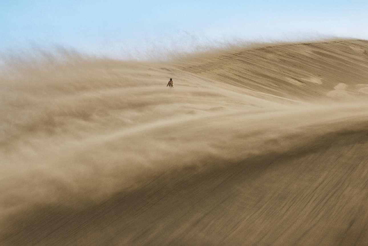 «Περιπλανώμενος». Θύελλα πάνω από τους αμμόλοφους που «τραγουδούν» - ένα φαινόμενο που παρατηρείται όταν περνάει αέρας πάνω από τους λόφους και παράγονται διάφοροι ήχοι, στο εθνικό πάρκο Altyn-Emel του Καζακστάν