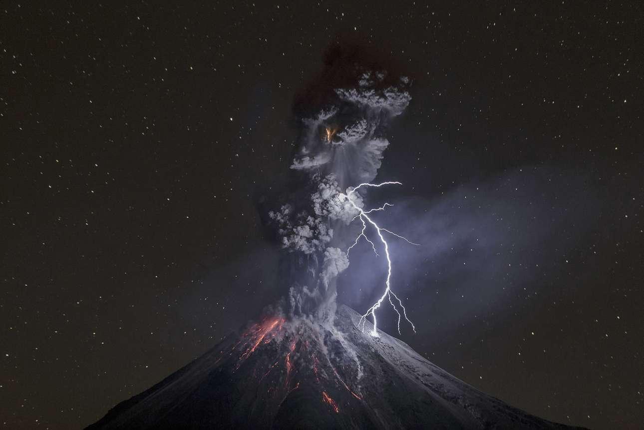 «Η Δύναμη της Φύσης». Η εντυπωσιακή έκρηξη του ηφαιστείου Κολίμα στο Μεξικό, τον Δεκέμβριο του 2015. «Εκείνο το βράδυ, η ξηρή ατμόσφαιρα και οι χαμηλές θερμοκρασίες σε συνδυασμό με τα σωματίδια στάχτης προκάλεσαν έναν τεράστιο κεραυνό 600 μέτρων, ο οποίος φώτισε ολόκληρο το σκοτεινό τοπίο» εξηγεί ο φωτογράφος στη λεζάντα που συνοδεύει την καταπληκτική αυτή εικόνα