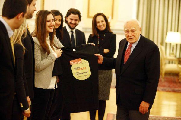 """Ο τ. ΠτΔ Κάρολος Παπούλιας υπογράφει την δράση του ΔΙΚΤΥΟΥ """"Invest In Education"""" και λαμβάνει δώρο αναμνηστικό μπλουζάκι από ομάδα νέων του ΔΙΚΤΥΟΥ"""