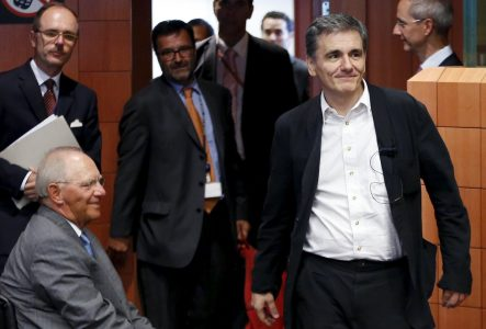 Greek Finance Minister Euclid Tsakalotos (R) walks past his German counterpart Wolfgang Schaeuble (L) at the start of a euro zone finance ministers meeting in Brussels, Belgium, August 14, 2015. Euro zone finance ministers will discuss whether to agree a third bailout package for Greece on Friday at their meeting in Brussels after the Greek parliament voted to approve the terms. REUTERS/Francois Lenoir