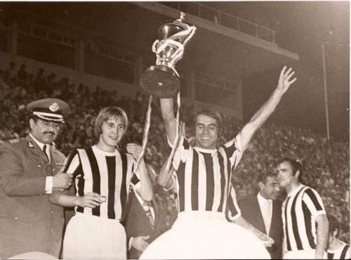 Ο Γιώργος Κούδας , ηγέτης και σκόρερ των δύο γκολ του ΠΑΟΚ κατά του Παναθηναϊκού (2-1) στον τελικό , σηκώνει το Κύπελλο στο Στάδιο Καραϊσκάκη. Αριστερά ο Γούναρης, δεξιά ο Παπαδόπουλος