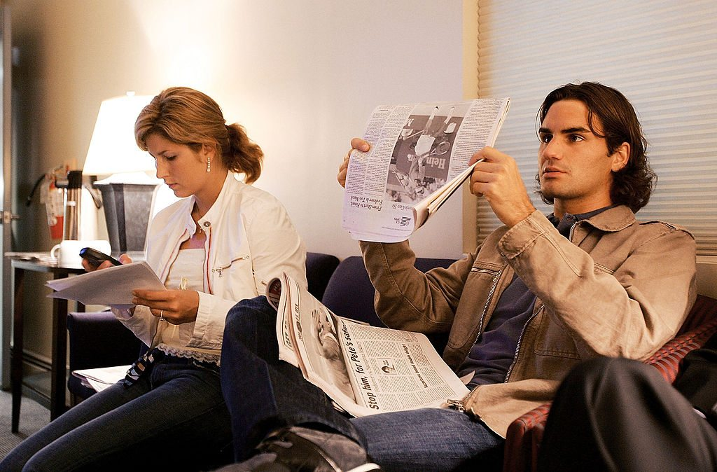 NEW YORK - SEPTEMBER 13: Roger Federer of Switzerland reads the newspapers while his girlfriend Mirka Vavrinec works the phone before Federer's apparence on the CBS Early Show on September 13, 2004 in New York City. Federer defeated Lleyton Hewitt of Australia yesterday to win the US Open and his third Grand Slam title of the year. (Photo by Ezra Shaw/Getty Images)