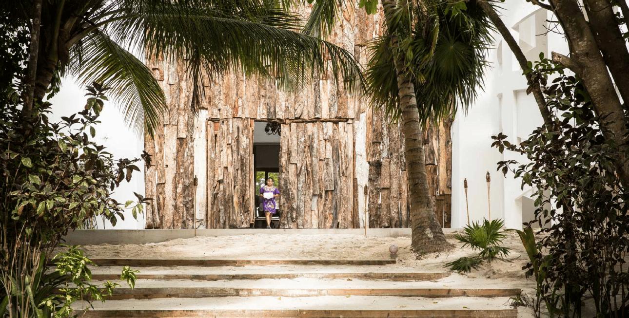 Αυτή είναι η είσοδος της Casa Malca. Καμουφλαρισμένη με κορμούς δέντρων. Προσέξτε την άμμο στα σκαλοπάτια... Την πατάς, τρυπώνει στο παπούτσι κι εσύ βουτάς σε κλίμα διακοπών προτού καν μπεις μέσα στον χώρο του ξενοδοχείου