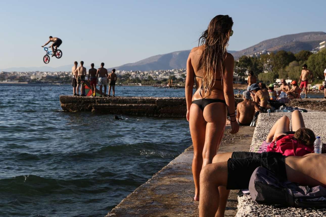 Οι λουόμενοι κοιτούν τους νέους που πηδούν στην θάλασσα με τα ποδήλατά τους