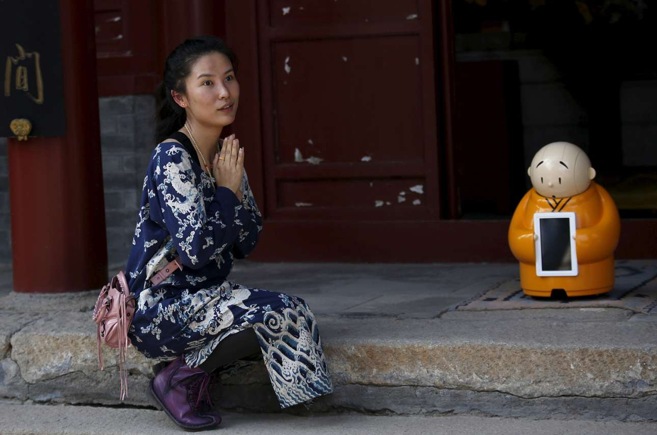 Μία επισκέπτρια παρακαλεί το προσωπικό να την αφήσει να βγάλει μία φωτογραφία μαζί με το χαριτωμένο ρομπότ που βρίσκεται στην υποδοχή του βουδιστικού ναού Λονγκουάν, στα προάστια του Πεκίνου