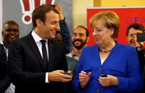 French President Emmanuel Macron offers a soft ball to German Chancellor Angela Merkel as they visit the Franco-German Youth Office (OFAJ) in Paris, France, July 13, 2017.  REUTERS/Matthieu Alexandre/Pool