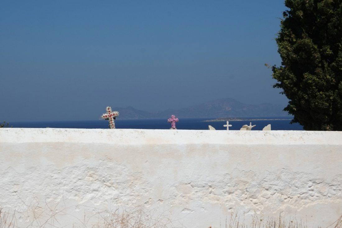 Μια εικόνα αντιθέσεων, η θλίψη του θανάτου και η χαρά του καλοκαιριού. Πίσω από το κοιμητήριο στο χωριό Πάλοι της Νισύρου, διακρίνεται το μπλε του Αιγαίου και η Κως