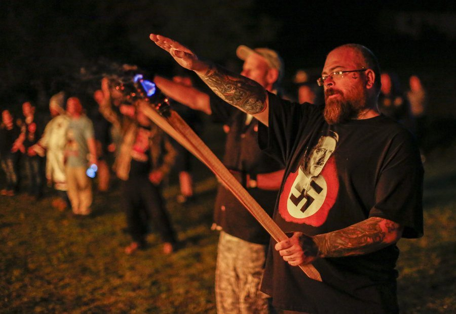 epa05275344 A picture made available on 24 April 2016 shows a man participates as pro-white rights organizations the neo-nazi National Socialist Movement and Ku Klux Klan groups participate in a cross and swastika burning in Temple, Georgia, USA, 23 April 2016. The ceremony was held after a day of rallies at Stone Mountain and Rome, Georgia, and to show successful collaboration agreements between the NSM and KKK, two white extremist groups. EPA/ERIK S. LESSER