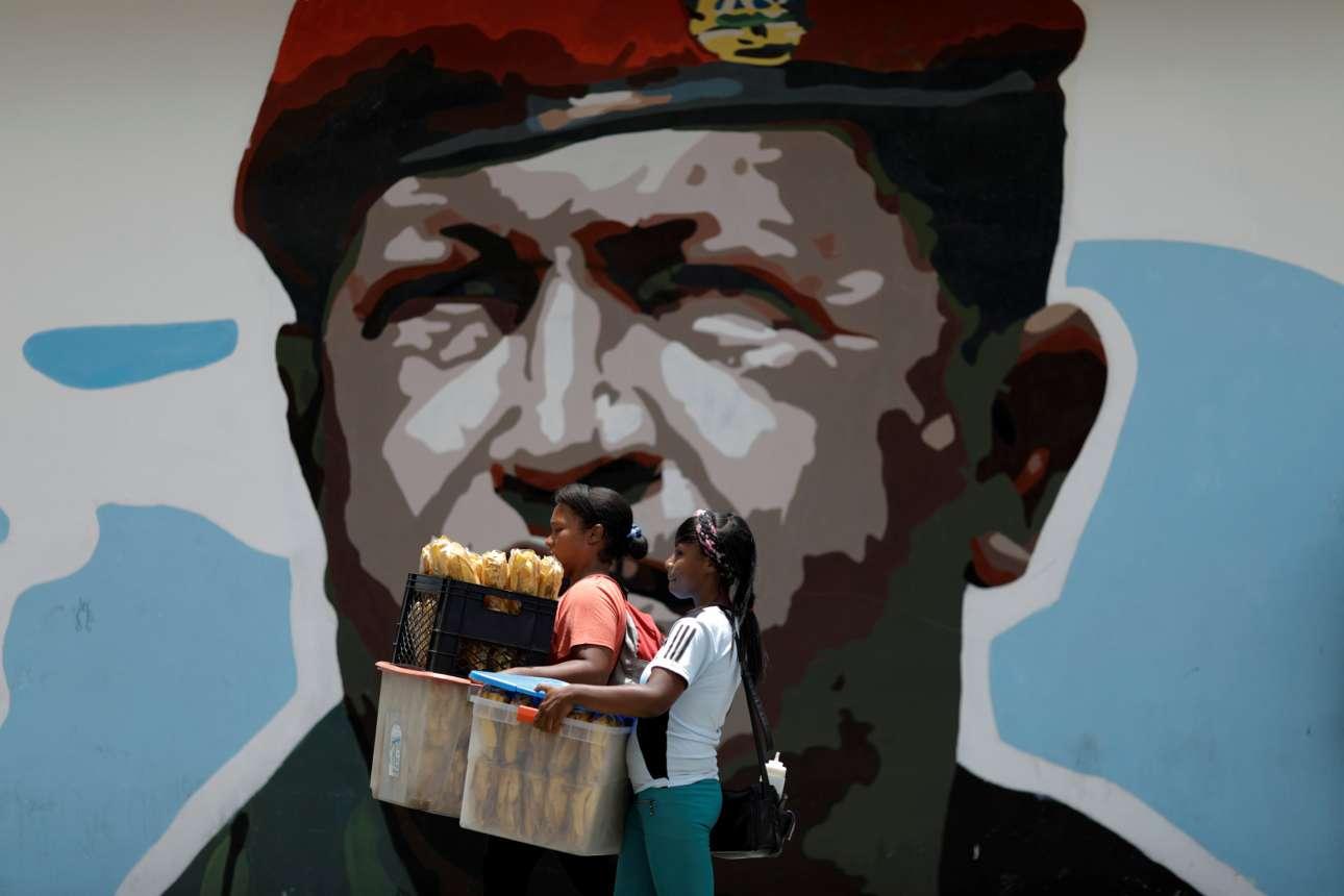 Δευτέρα, 7 Αυγούστου. Δύο γυναίκες περνούν μπροστά από τοιχογραφία του Ούγκο Τσάβες στο Καράκας της Βενεζουέλας. Η χώρα της λατινικής Αμερικής βιώνει μία από πιο ταραχώδης περιόδους στην ιστορία της