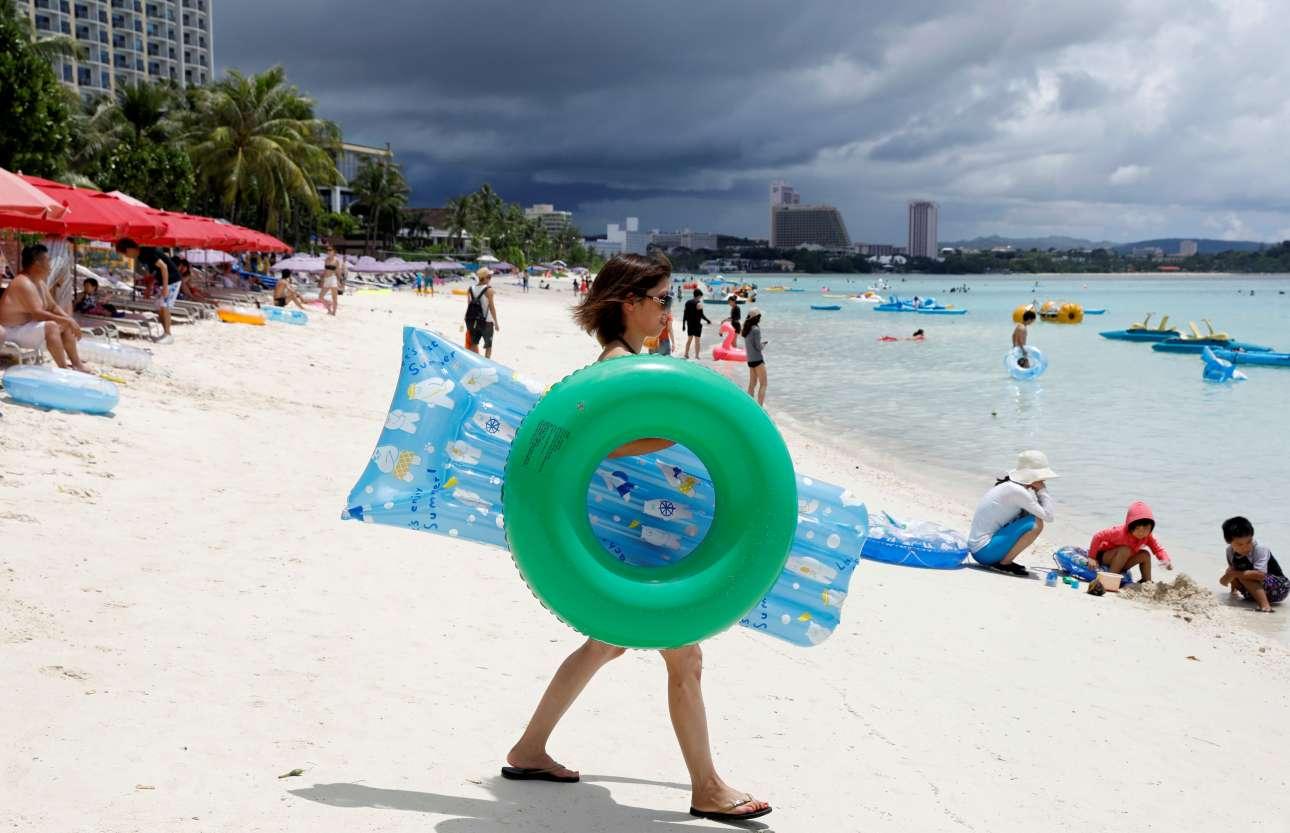 Πέμπτη, 10 Αυγούστου. Τουρίστας κατευθύνεται προς την παραλία Τουμόν στην νήσο Γκουάμ. Ο ουρανός πίσω της δεν δείχνει και ιδιαίτερα καλοκαιρινός