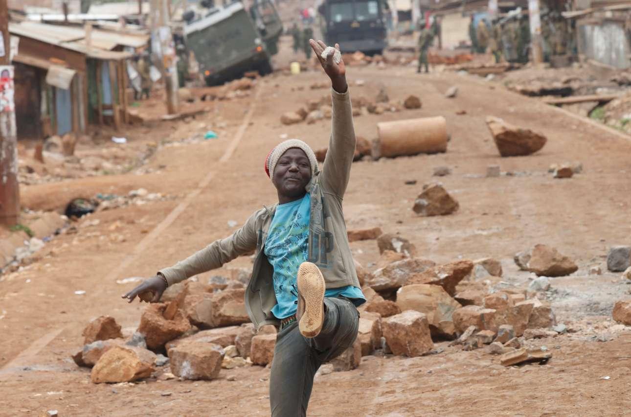 Πέμπτη, 10 Αυγούστου. Χαμογελώντας μπροστά στο χάος. Ενας υποστηρικτής του ηγέτη της αντιπολίτευσης της Κένιας, Ράιλα Οντίνγκα ποζάρει με φόντο τα οδοφράγματα κατά τη διάρκεια αντικυβερνητικών διαδηλώσεων