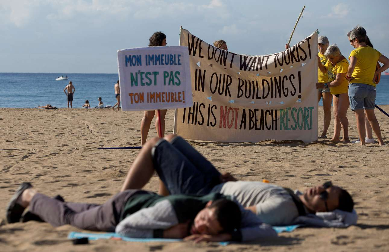 Σάββατο, 12 Αυγούστου, Βαρκελώνη. Ντόπιοι διαμαρτύρονται με πανό γραμμένα στα γαλλικά και στα αγγλικά κατά του μαζικού τουρισμού. «Τα έπιπλά μου δεν είναι και δικά σου έπιπλα» - «Δεν θέλουμε τουρίστες στα κτίριά μας, αυτό δεν είναι παραλία θερέτρου» γράφουν.