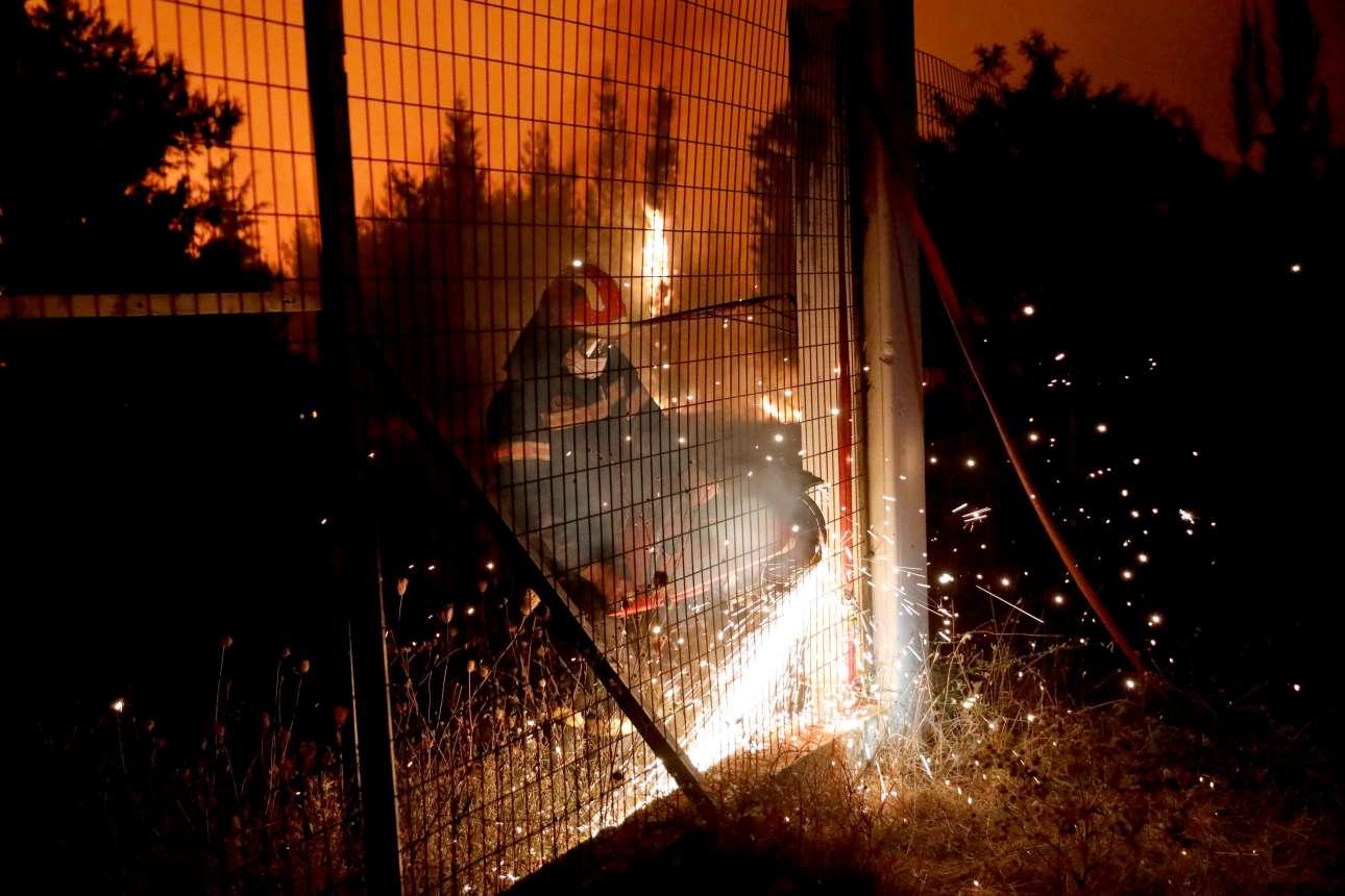 Φωτιά στη φωτιά, σπίθες στις σπίθες. Με το αλυσοπρίονο προσπαθεί να κόψει έναν φράκτη, να βρει δίοδο στη φωτιά...