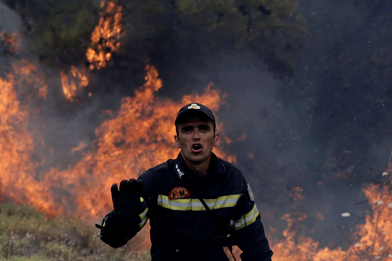 Ανήμερα Δεκαπενταύγουστος, με φόντο τις φλόγες ο πυροσβέστης προσπαθεί να απομακρύνει τον κόσμο