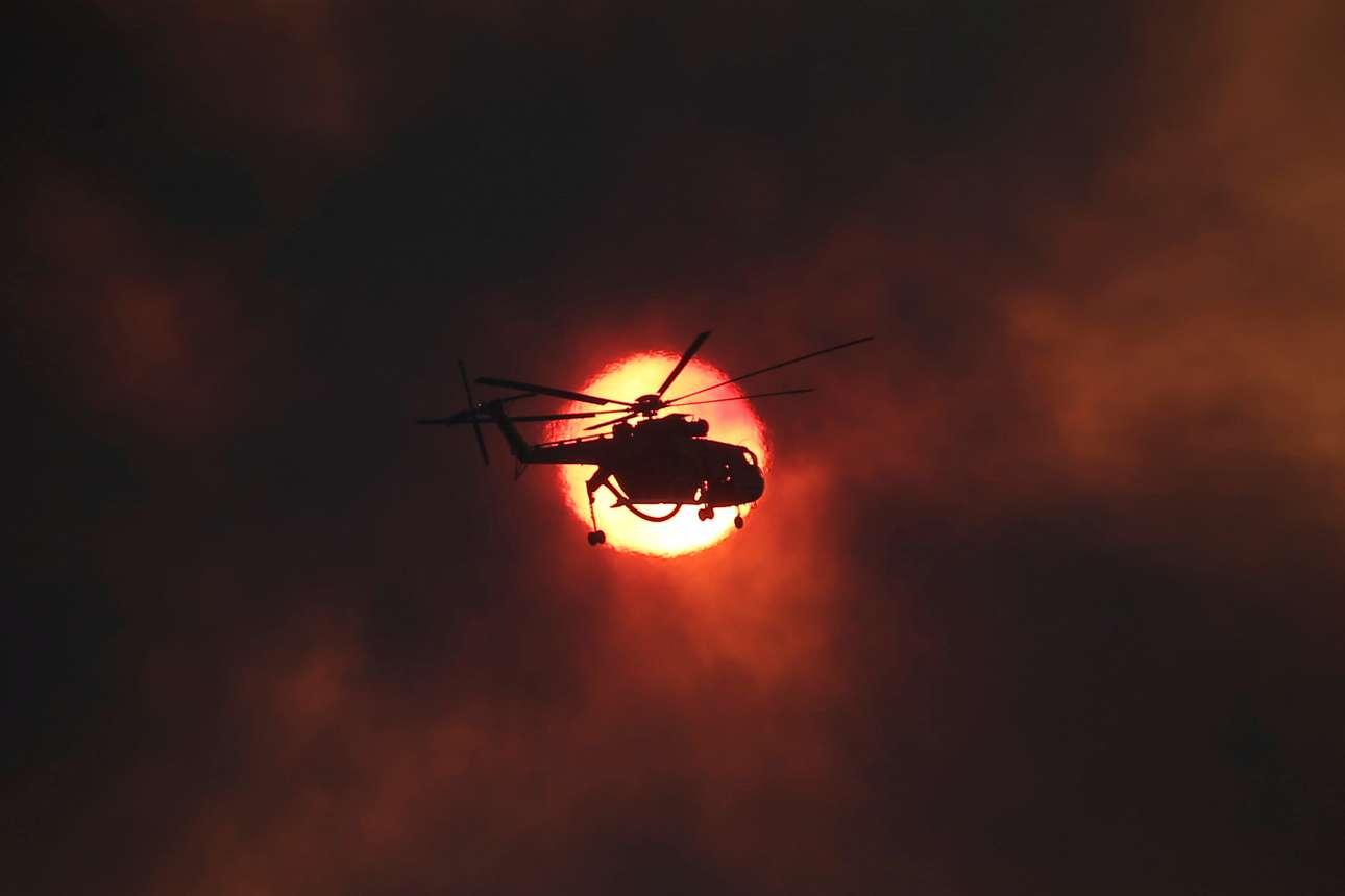 Τρίτη, 15 Αυγούστου. Ενα ελικόπτερο κατάσβεσης περνά μπροστά από τον ήλιο πάνω από το Καπανδρίτι. Οι πυκνοί καπνοί από την καταστροφική φωτιά υψώνονται στον ουρανό