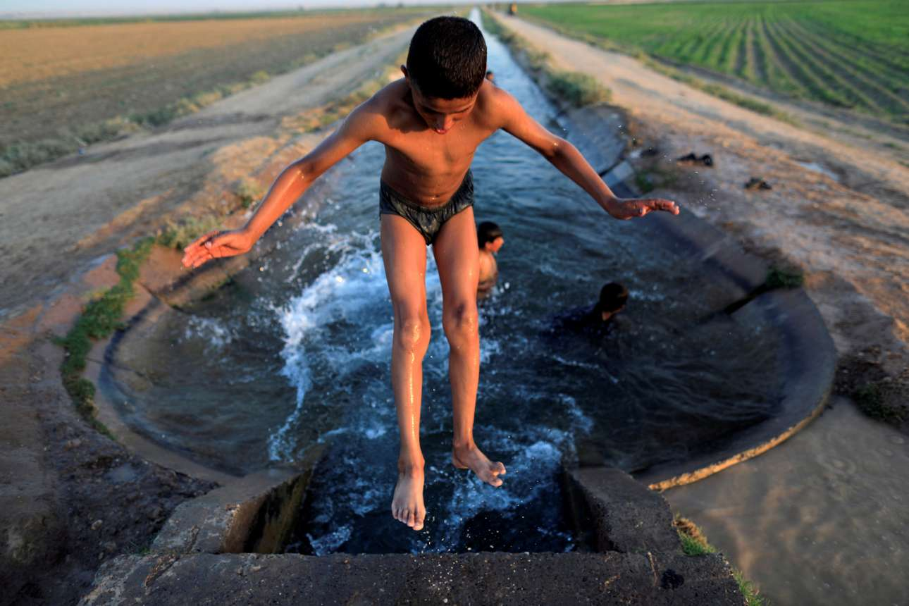 Τετάρτη, 16 Αυγούστου. Πιτσιρίκια κάνουν μπάνιο σε ένα κανάλι ύδρευσης έξω από την Ράκα της Συρίας
