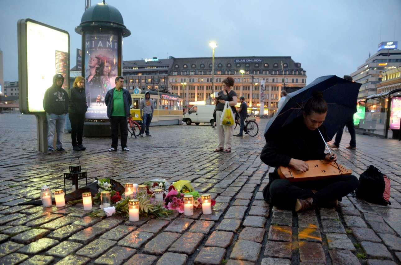 Σάββατο, 19 Αυγούστου. Γυναίκα παίζει ένα παραδοσιακό μουσικό όργανο της Φινλανδίας προς τιμήν των ανθρώπων που μαχαιρώθηκαν την προηγούμενη ημέρα στην πόλη Τούρκου της Φινλανδίας