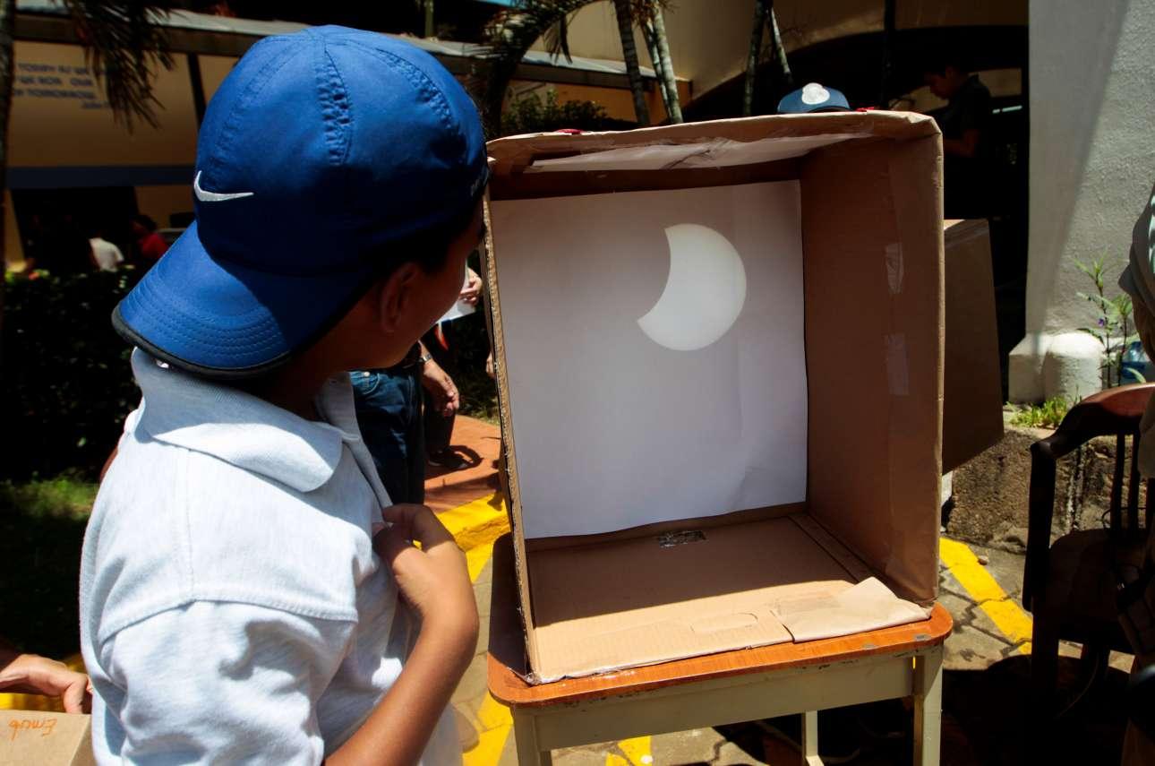 Ενας μαθητής θαυμάζει την έκλειψη μέσα από ένα χάρτινο κουτί, στη Μανάγκουα της Νικαράγουα