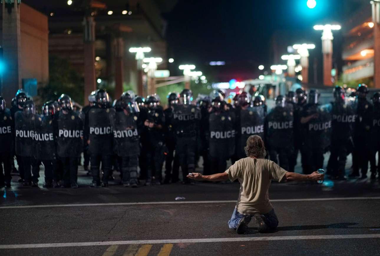 Τρίτη, 22 Αυγούστου. Ενας διαδηλωτής στέκεται γονατιστός μπροστά στις αστυνομικές δυνάμεις στις ΗΠΑ την ώρα που ο Ντόναλντ Τραμπ μιλάει σε συγκέντρωση στο Φοίνιξ της Αριζόνα