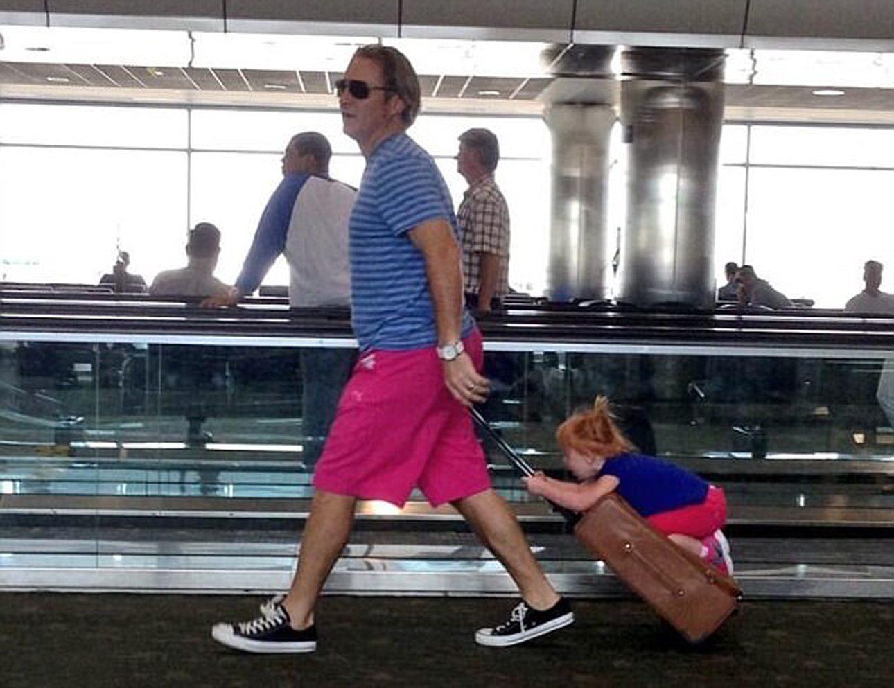 Ο μπαμπάς της φωτογραφίας το διασκεδάζει με την κόρη του, μεταφέροντας την στο αεροδρόμιο πάνω στη βαλίτσα