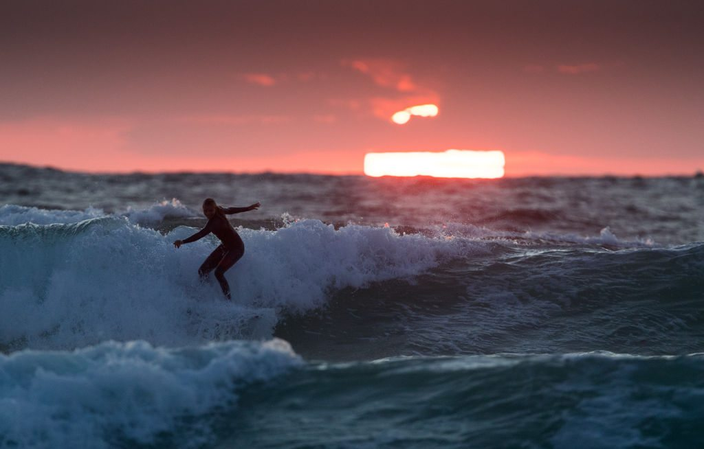 Τετάρτη, 9 Αυγούστου. Ενας σέρφερ απολαμβάνει τα κύματα με φόντο ένα κατακόκκινο ηλιοβασίλεμα στην παραλία Φιστράλ της αγγλικής πόλης Νιουκουέι. Ολα αυτά κατά την πρώτη ημέρα του φεστιβάλ μουσικής Boardmasters