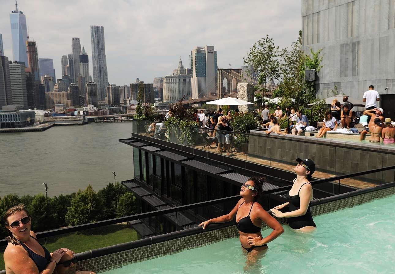 Παρατηρώντας την έκλειψη από πισίνα σε ταράτσα ξενοδοχείου στη Νέα Υόρκη. Τι άλλο να ζητήσει κάποιος από τις διακοπές του!