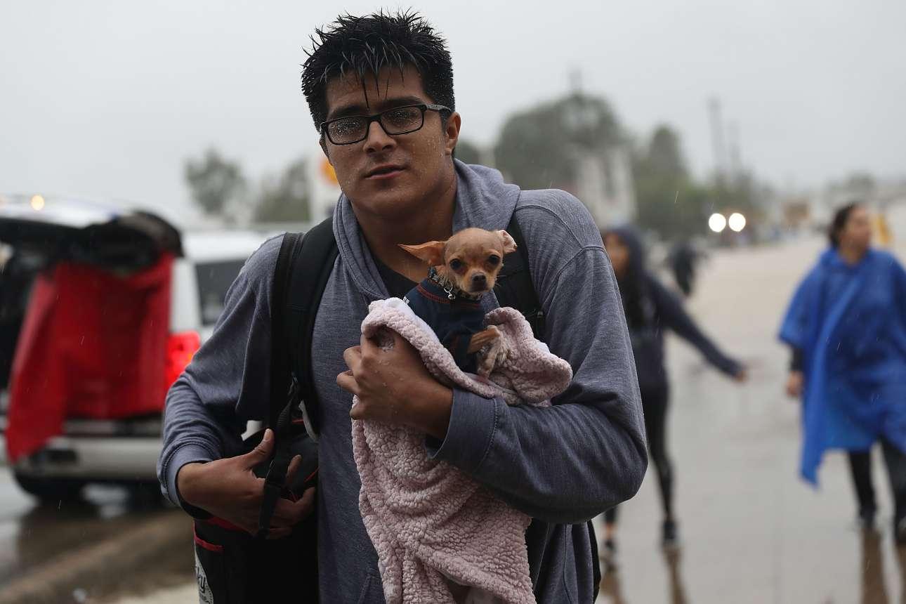 Ενας νεαρός έχει τυλίξει το μικροσκοπικό σκυλί του με μία πετσέτα για να μην κρυώσει. Την ίδια στιγμή, ο ίδιος μοιάζει βρεγμένος από την κορυφή ως τα νύχια